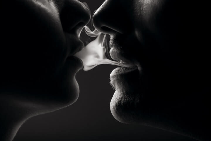 Young couple portrait sharing a smoke coming out from theirs mouth.